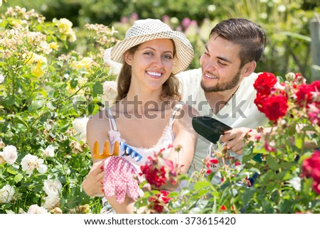 Portrait of smiling young couple working together in garden at summer day