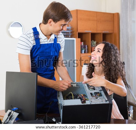Portrait of smiling young female and PC repairman fixing computer