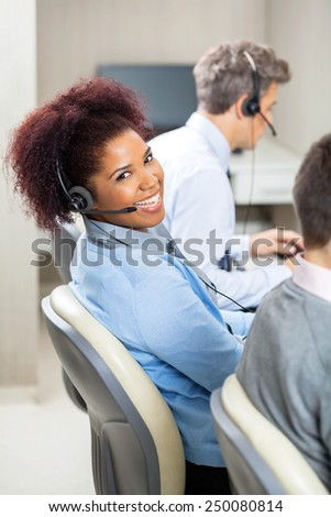 Portrait of smiling young female customer service representative with colleagues working in office - stock photo