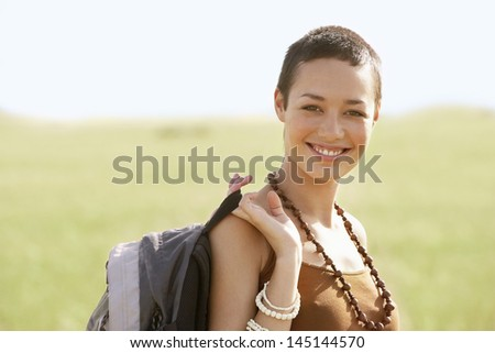Portrait of smiling young female hiker with backpack in field - stock photo