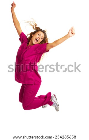 Portrait of smiling young female nurse throwing apple over white background
