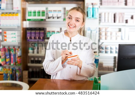 Portrait of smiling young female pharmaceutist working in modern farmacy