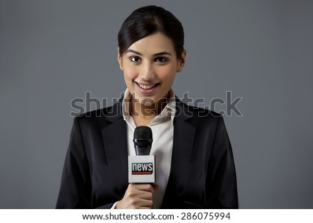 Portrait of smiling young female TV reporter against colored background - stock photo