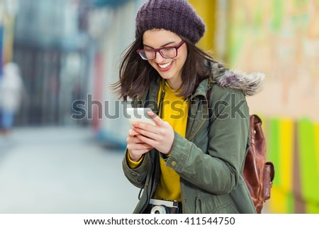 Portrait of smiling young hipster woman using her mobile phone on the street of old town - stock photo