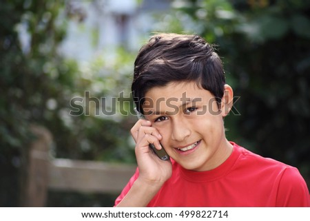 Portrait of smiling young Hispanic boy on a cell phone or mobile - taken with vintage lens