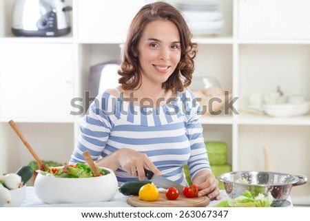 Portrait of smiling young housewife preparing salad
