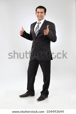 Portrait of smiling young indian business man giving thumbs up sigh with both hands - stock photo