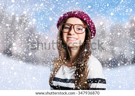 Portrait of smiling young lady wearing striped sweater red hat and glasses on winter background with falling snowflakes