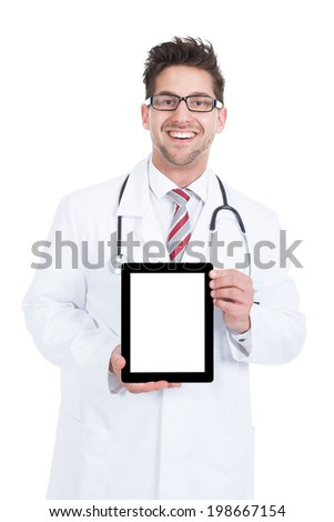 Portrait of smiling young male doctor displaying digital tablet over white background - stock photo