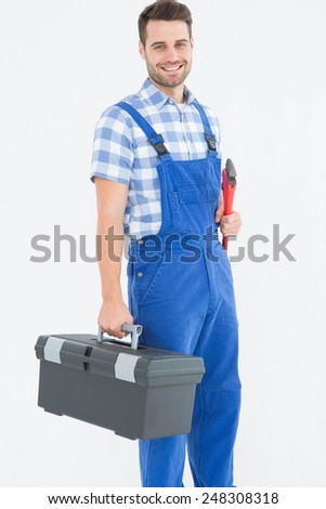 Portrait of smiling young male repairman carrying toolbox on white background - stock photo