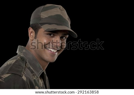 Portrait of smiling young male soldier against black background - stock photo