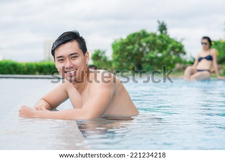 Portrait of smiling young man at the edge of the swimming pool, his girlfriend is sitting in background - stock photo