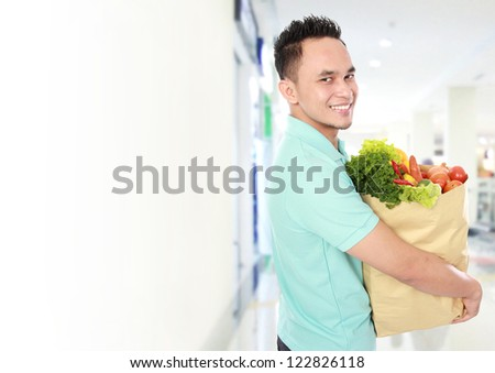 Portrait of smiling young man holding grocery bag full of groceries in supermarket - stock photo