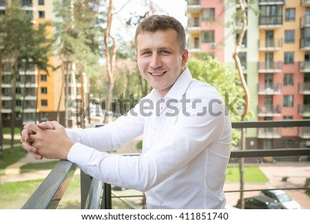 Portrait of smiling young man in white shirt posing on balcony at sunny day - stock photo