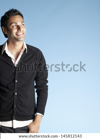Portrait of smiling young man looking up at copyspace isolated on blue background