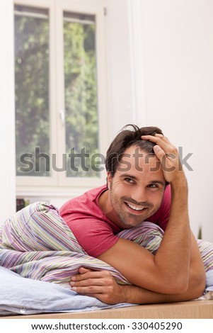 Portrait of smiling young man lying on his bed