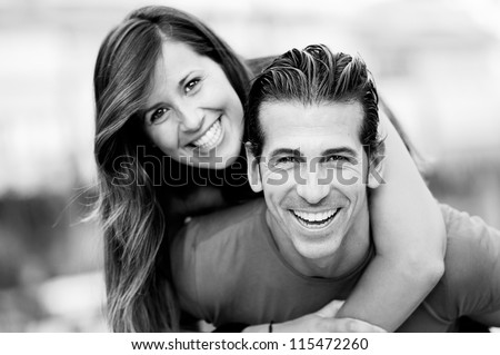 Portrait of smiling young man piggybacking his pretty girlfriend in the park