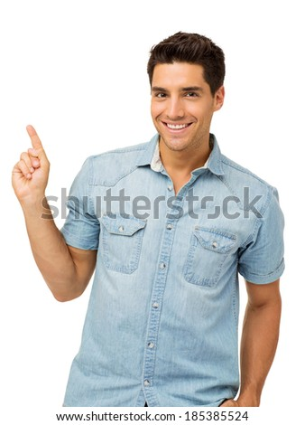 Portrait of smiling young man pointing upwards while standing against white background. Vertical shot. - stock photo