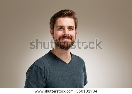 Portrait of smiling young man with beard, on neutral background