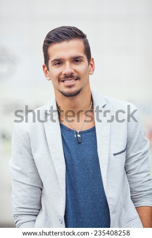 Portrait of smiling young man with hands in pockets - stock photo