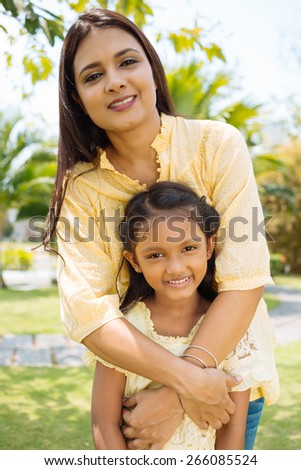 Portrait of smiling young mother embracing her little daughter - stock photo