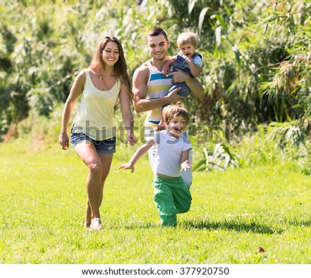 Portrait of smiling young parents with two children in summer park. Focus on girl