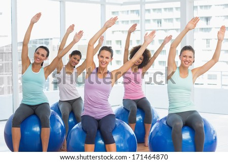 Portrait of smiling young people sitting on exercise balls in the bright gym