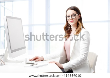 Portrait of smiling young professional woman typing on keyboard while working on computer.  - stock photo