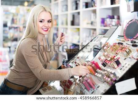 Portrait of smiling young russian blondie selecting lipstick in store