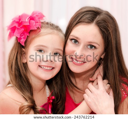 Portrait of smiling young woman and her little girl  - stock photo