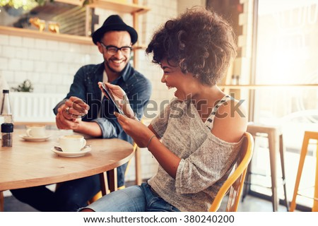 Portrait of smiling young woman at a cafe table looking at digital tablet with a friend sitting by.