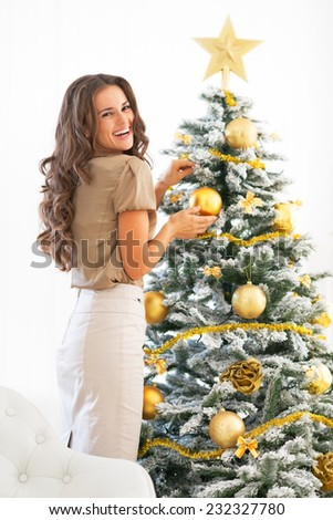 Portrait of smiling young woman decorating christmas tree - stock photo