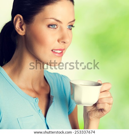Portrait of smiling young woman drinking coffee, outdoor