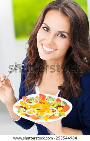 Portrait of smiling young woman eating vegetarian vegetable salad - stock photo