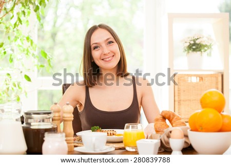 Portrait of smiling young woman having breakfast at home - stock photo
