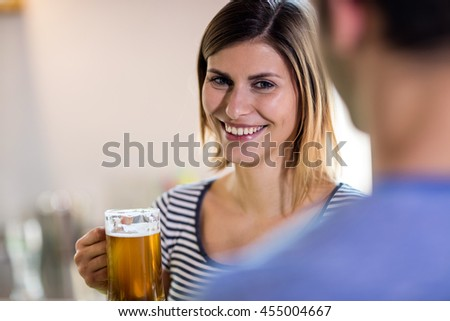 Portrait of smiling young woman holding beer mug in bar