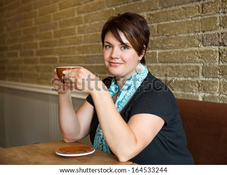 Portrait of smiling young woman holding coffee cup in cafeteria - stock photo