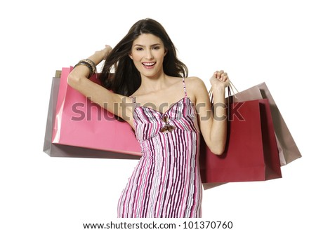 Portrait of smiling young woman holding colorful shopping bags