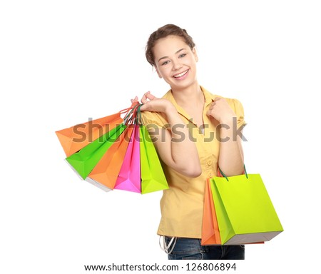 Portrait of smiling young woman holding colourful shopping bags against white background