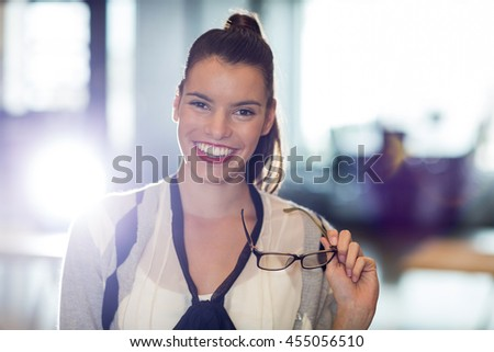 Portrait of smiling young woman holding eyeglass in office - stock photo