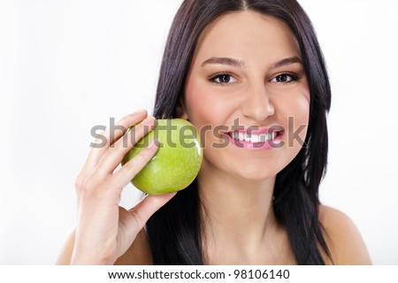 Portrait of smiling young woman holding fresh organic green apple, beautiful toothy smile with extremely white teeth