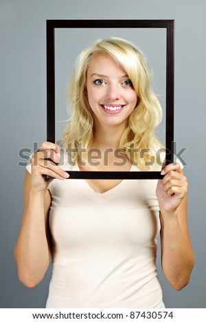 Portrait of smiling young woman holding picture frame on grey background - stock photo