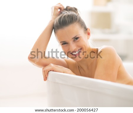 Portrait of smiling young woman in bathtub