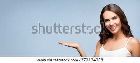Portrait of smiling young woman in white casual clothing showing copyspace or something, over grey background - stock photo