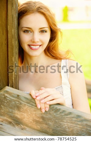 Portrait of smiling young woman, leans about wooden wall - stock photo