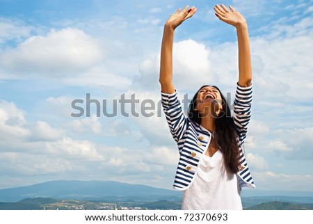 Portrait of smiling young woman lifted hands to sky - stock photo