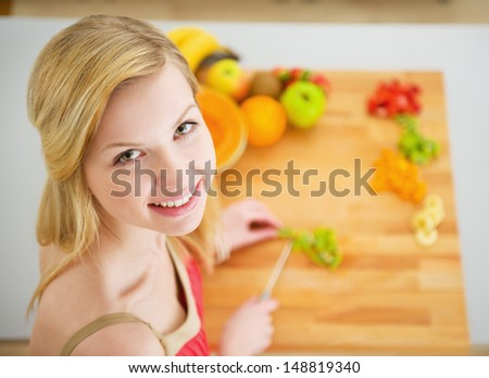 Portrait of smiling young woman making fruits salad