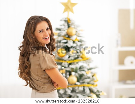 Portrait of smiling young woman near christmas tree - stock photo