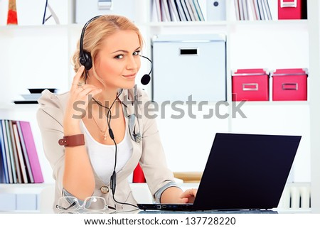 Portrait of smiling young woman operator in headset at office. - stock photo