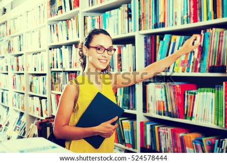 Portrait of smiling young woman picking textbooks for school in book shop